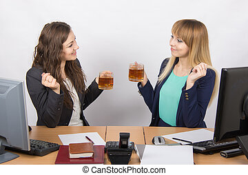 The conversation over tea two office employees at the desk -...