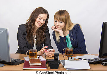 Two office girls discuss personal matters and drinking tea at your desk