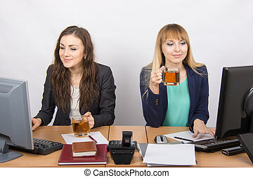 Two office girl working at computers in the hands of tea -...