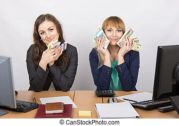 Two office staff member at the table cuddle money packs