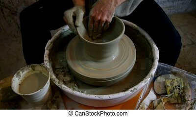 ceramist potter lathe - hands shaping a clay pottery bowl on...