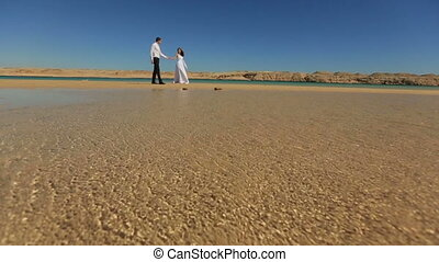 Happy bride and groom walking on the beach in Egypt. Exotic...