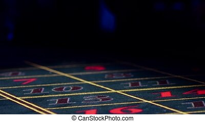 Hands bet chips, one fall down on roulette table, black -...