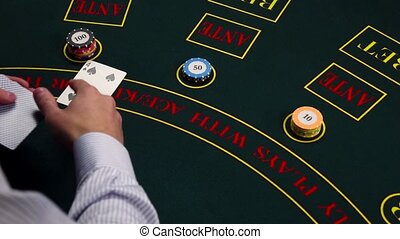 Croupier deal cards on green table with chips at casino