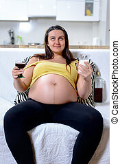Pregnant woman holding wine and milk - Front view of...