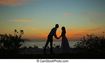Silhouettes of wonderful couple holding hands and kissing. Romantic sunset on background