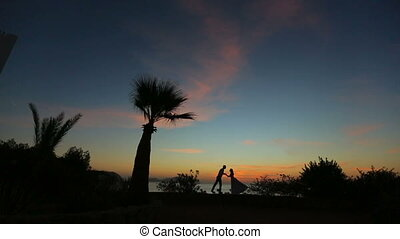 Silhouettes of beautiful wedding couple kissing on sunset....