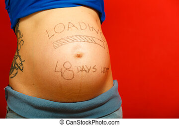 Pregnant woman with loading concept painted on her belly -...