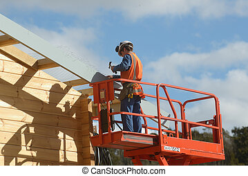 preparing for the roof - A builder attaches wire netting to...