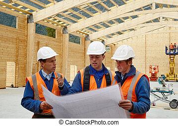 builders study the plan - Three builders discuss the plan...