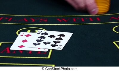 Player bets chips on poker table with cards, slow motion -...