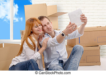 Happy couple sitting on the floor taking selfie in their new house