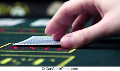 Player checks his cards playing poker, close up, slow motion...