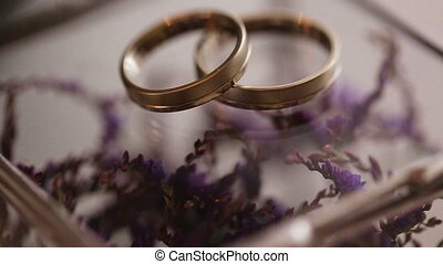 Close up of gold wedding rings on purple flowers backround.