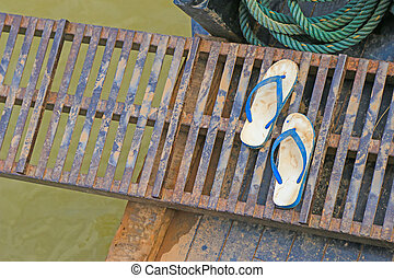 Wet dirt on rubber slippers on a portable metal gangway...