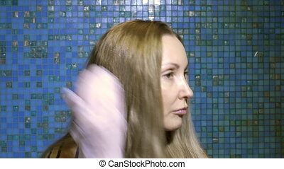 The woman applying hair coloring dye at home herself. Applies the painting mix with a hand in a glove on hair. 4k video