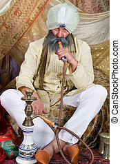 Water pipe - Arab with turban demonstrating a water pipe