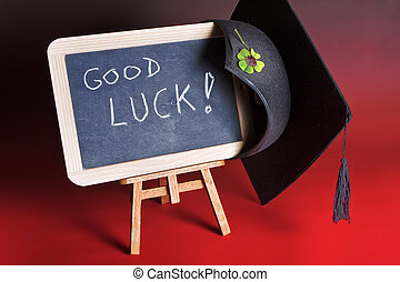 Good luck board - Graduation cap haning on a blackboard with...