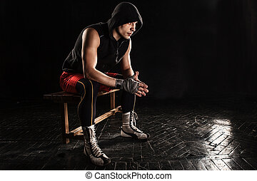 The muscular man sitting and resting on black - The muscular...