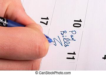Pay Bills - The man\'s hand makes entry in calendar Pay...