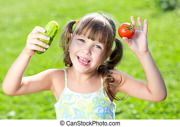Adorable little girl with vegetables outdoor