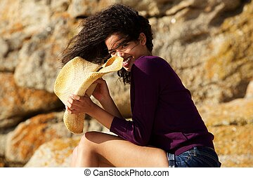 Beautiful black woman smiling outdoors with hat