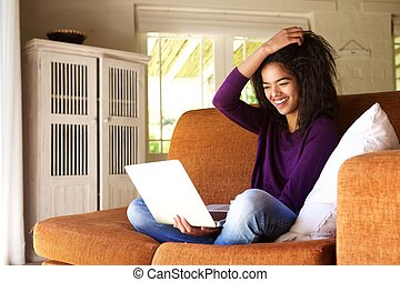 Portrait of a smiling female student sitting at home working...
