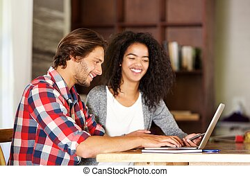 Smiling man and woman working with laptop