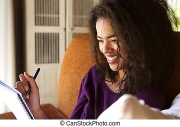 Smiling female student writing in diary - Close up portrait...