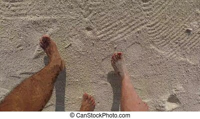 couple feet walking along sandy beach