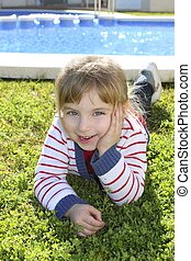 blond little girl laying on pool grass posing