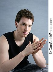 casual young man portrait sit over gray grunge background