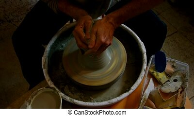 potter lathe  - hands shaping a clay pottery bowl on wheel