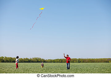 Family running with a kite.