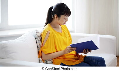 smiling young asian woman reading book at home - leisure,...