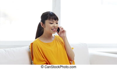 happy asian woman calling on smartphone at home