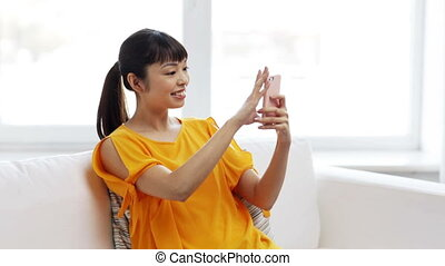 happy asian woman taking selfie with smartphone