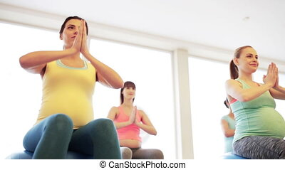 happy pregnant women exercising on fitball in gym -...