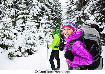 Couple hikers trekking in winter woods - Man and woman happy...
