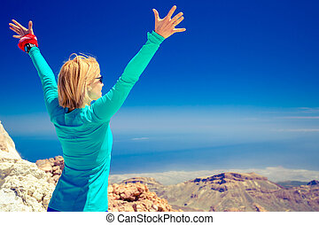 Hiking success, arms up outstretched in mountains - Woman...