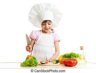 Child girl is cutting vegetables for salad using kitchen knife, isolated over white
