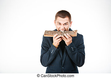 Businessman biting wooden timber isolated on a white...