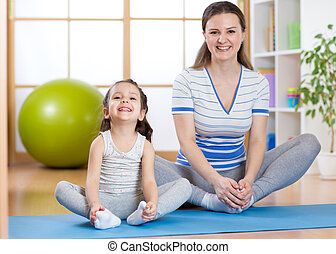 Happy mom and child spends time in the gym