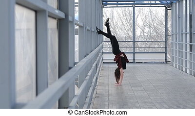 Sport woman doing gymnastics, standing on the street in the hands
