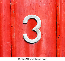 White number 3 sign on a red wooden door
