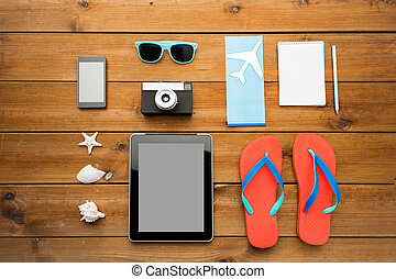 close up of tablet pc and travel stuff - vacation, travel,...