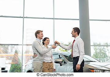 Dealership - Young couple with car keys indoors