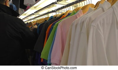 Man is choosing a t-shirt - Man in black coat at the clothes...