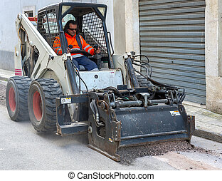 Small milling machine removing an old pavement layers at...