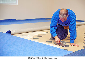 spreading the glue - floorlayer spreading adhesive on the...
